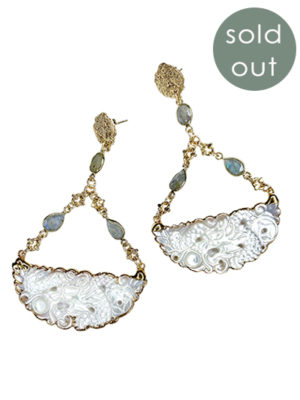 "a set of earrings with two large half circles of pearls flattened with a gold chain and two smaller pearlescent stones leading to a gold earring hook with a ""sold out"" graphic"